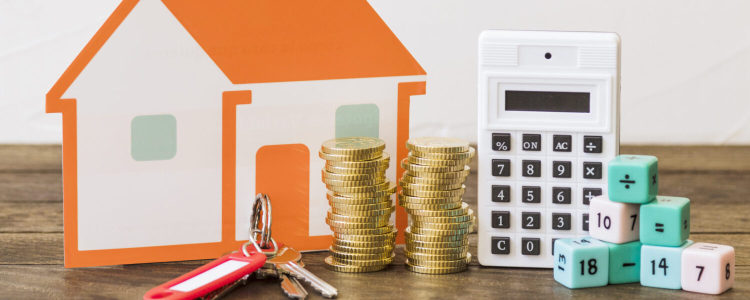 house-key-stacked-coins-calculator-math-blocks-wooden-table